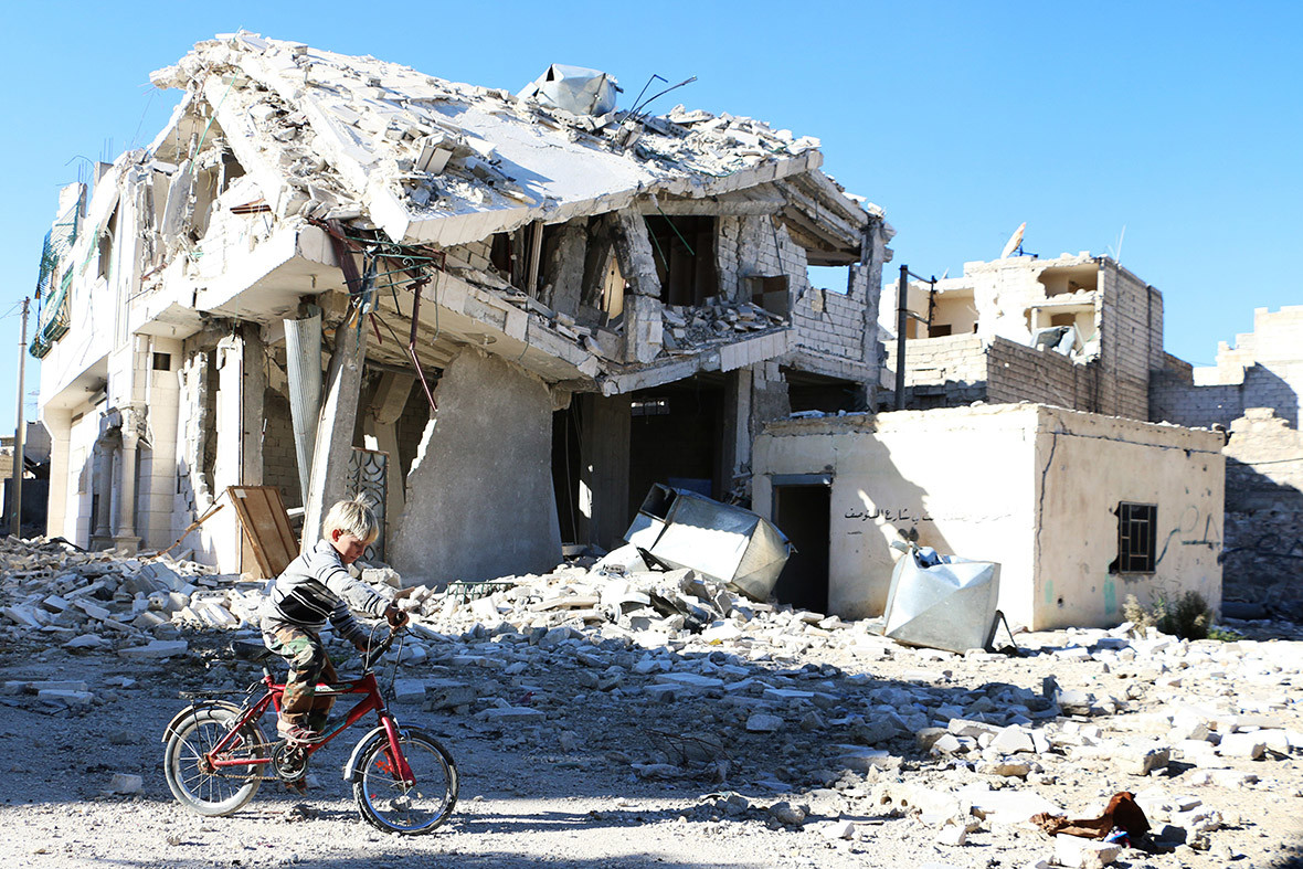 A boy rides his bike past a destroyed building in Aleppo - AFP