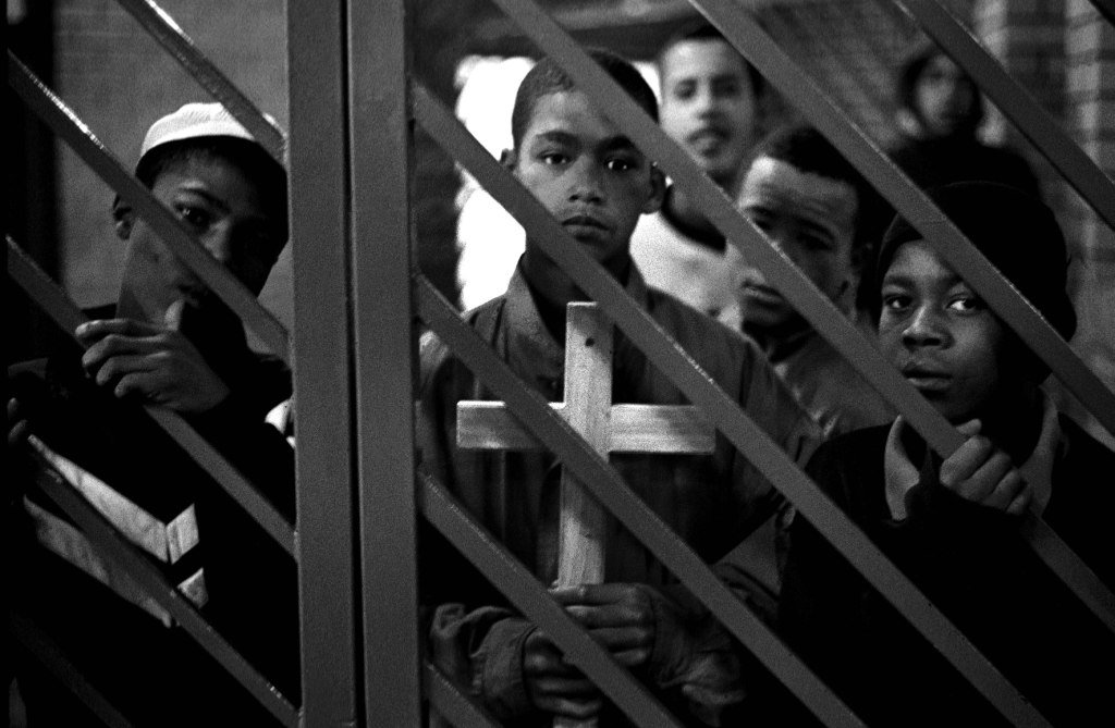 "Bosasa/ Horizon ""place of safety"" near cape Town. 2001. Inmates at about six in the morning at one of the gates to the outside world wait for the the various police investigating officers who will take them to court (s) for their trials. The child holding the cross has made it himself in the wood work class and will take this to court to give to his family as a small token in an attempt to heal the rifts he has caused by doing what ever crime he is accused of."