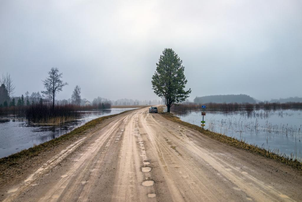 Soomaa. The wet fifth season between winter and spring brings a lot of visitors to this swampy region in the heart of Estonia. In some years, they get to paddle past the lone remaining houses, partially submerged in the slow flooding rivers. Water is everywhere — except on this Soviet-era road. Built in a totalitarian way as a mostly straight cut through the landscape, it turned upside down the structure of villages and shut down the old meandering small road between them.