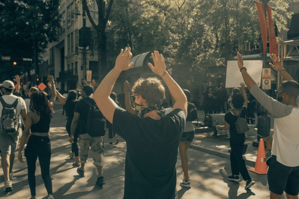 Demonstrators holding up their hands at a protest in Charlotte, NC. Photo by Clay Banks on Unsplash.