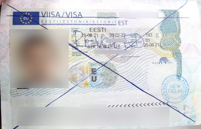 """Kamal's Estonian visa with lines drawn and the word """"REVOKED"""" written on it. We've blurred out the important details and his photo to protect his identity. Photo: courtesy of Kamal."""
